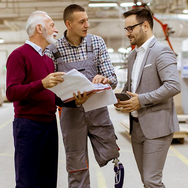A man with a prosthetic leg talks with two other men in a warehouse.